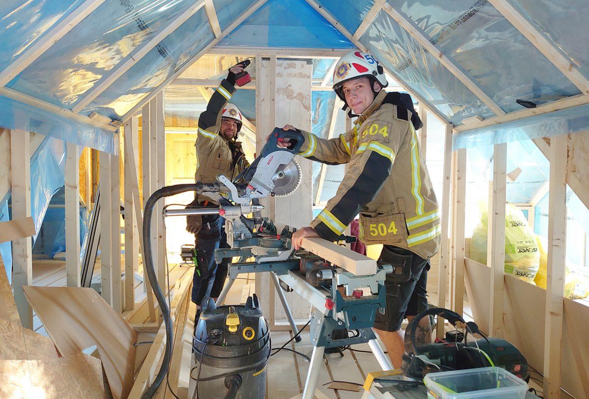 Två snickare som även arbetar som räddningstjänstpersonal i beredskap, arbetar i en byggarbetsplats klädda i brandmanshjälmar, larmställsjackor och snickarbyxor.