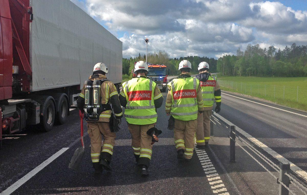 Ryggarna på fyra brandmän som går på väg vid trafikolycka.
