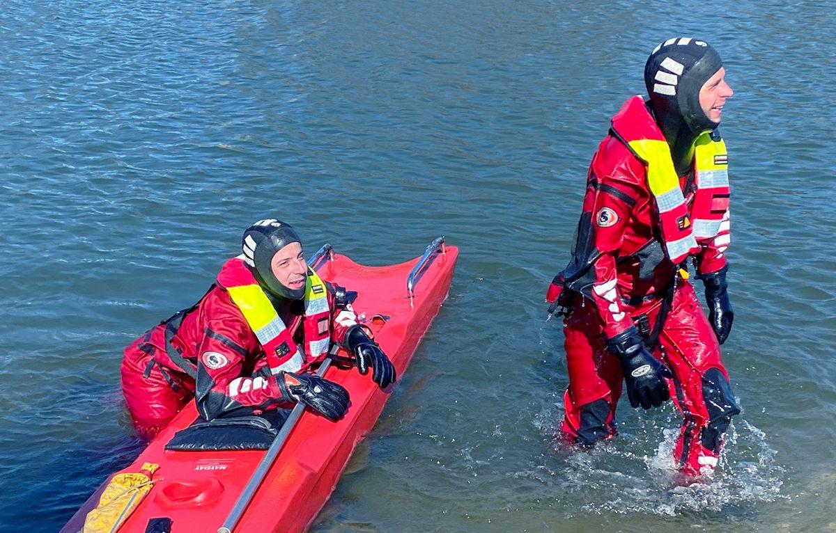 Två brandmän i torrdräkt i vatten. Övar vattenlivräddning med räddningsplanka.