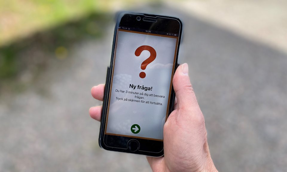 Hand som håller en mobiltelefon. På bildskärmen visas ett stort frågetecken och texten Ny fråga.
