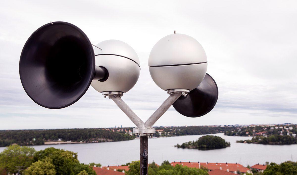 Sändare för utomhussignalen Viktigt meddelande till allmänheten, VMA. I bakgrunden utsikt över skog, vatten och bebyggelse.
