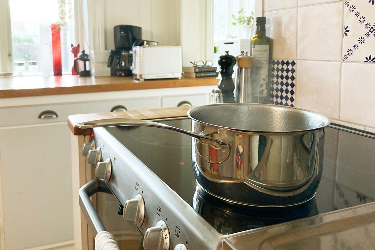 Kastrull som står på en spisplatta i kök.