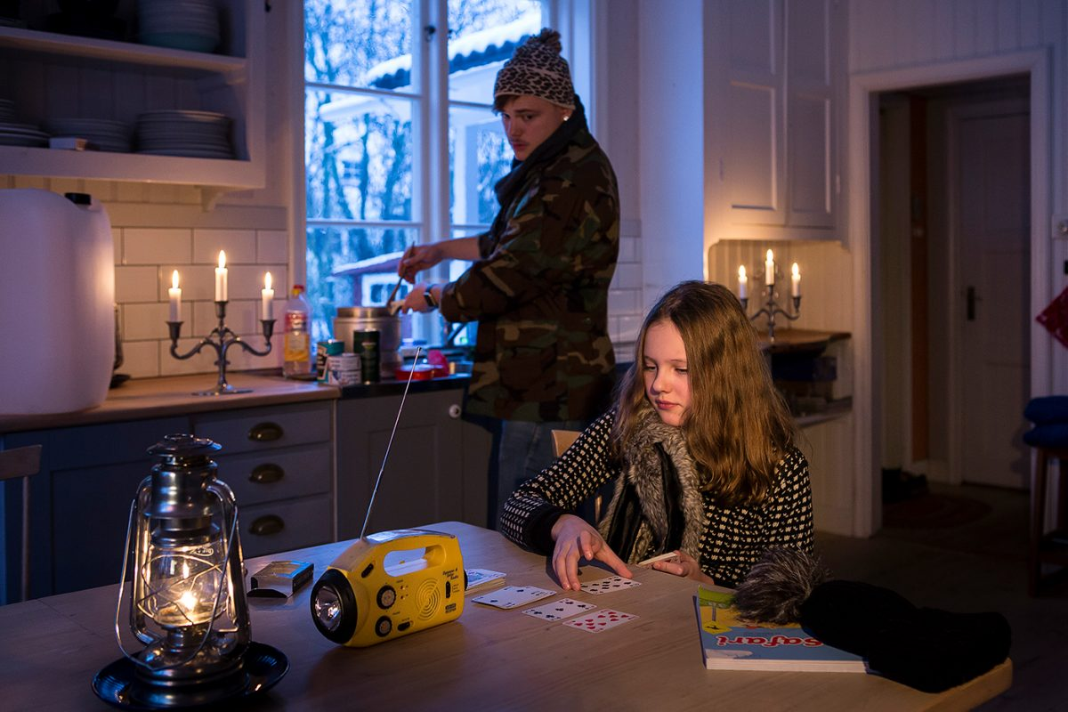 Två personer i nedsläckt hem. Tända ljus, fotogenlykta och matlagning på friluftskök.