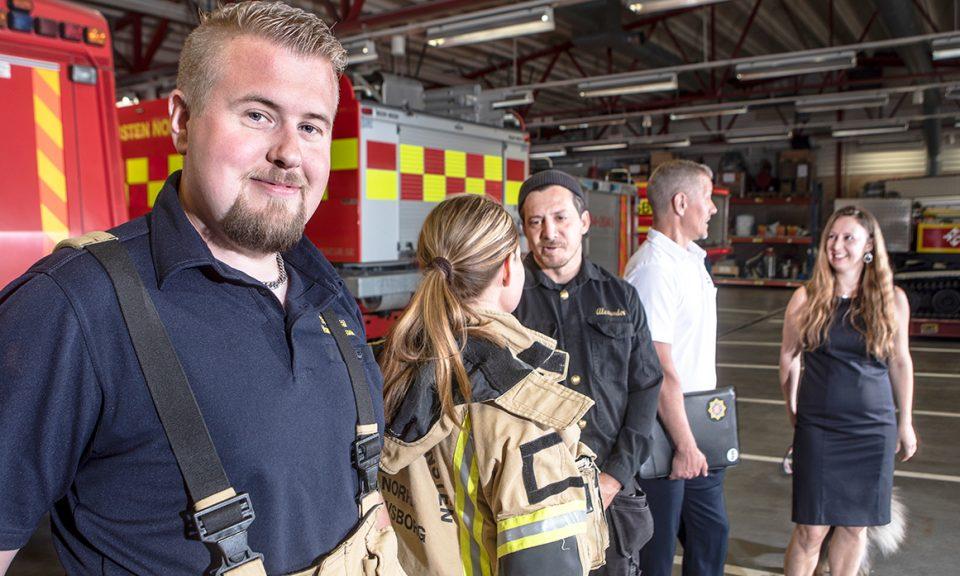 Fem personer i NÄRF uppställda med en brandman i förgrunden. Olika yrken representeras genom att personerna har olika kläder - brandmän, sotare och administrativ personal.