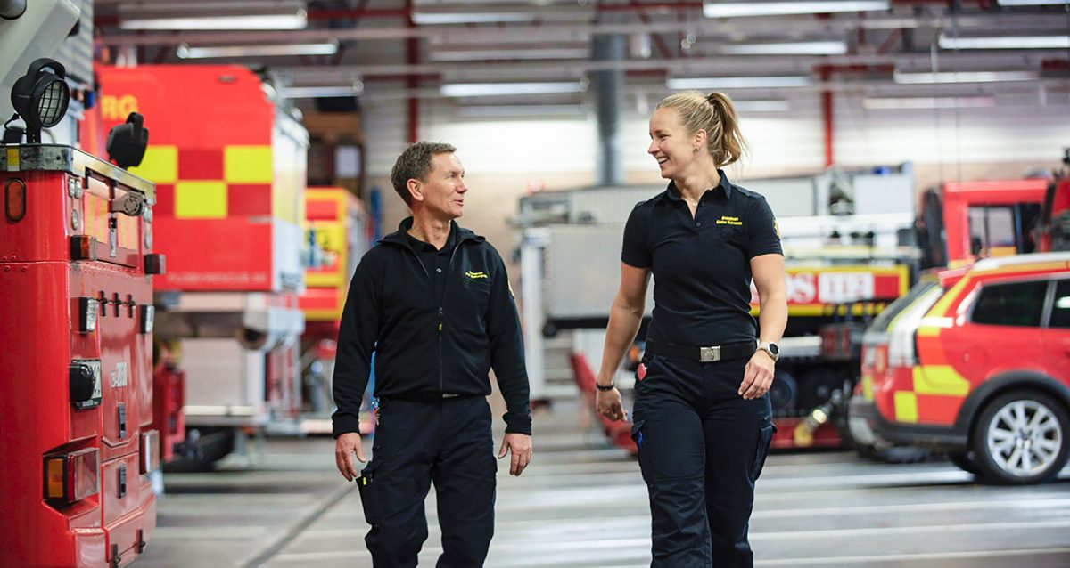 Två brandmän, en man och en kvinna, går framåt i en vagnhall med räddningstjänstfordon. Ler mot varandra.