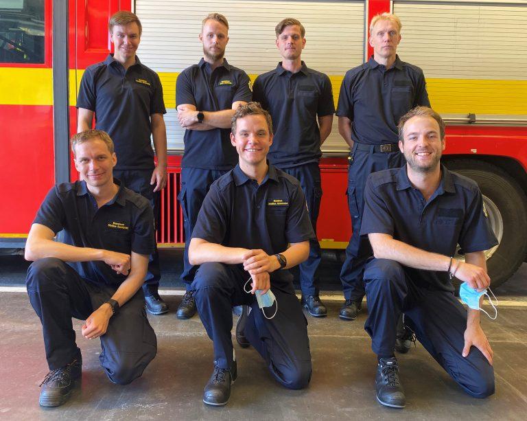 Sju brandmansvikarier uppställda framför en brandbil.