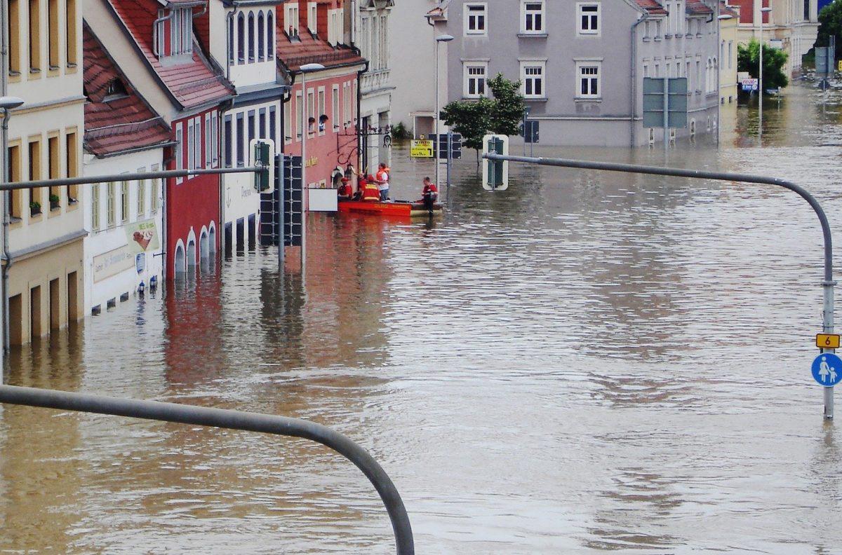 Översvämmad gata med flera husintill.