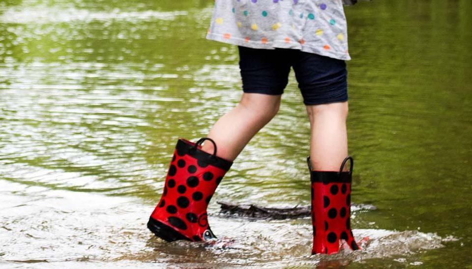 Barn med stövlar som går i vatten.